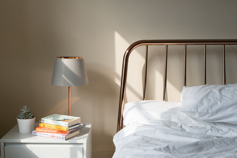 Side of bed and bedside table decorated with books, table lamp and succulent with sunlight shining through