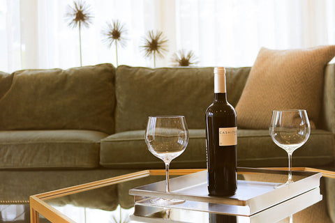 Close up of coffee table with wine bottle and two wine glasses with green sofa in background