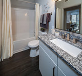 Towel Bar - 24 Inch - Stainless Steel - Minimalist Design installed in bathroom between tube and mirror and above the toilet