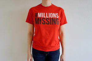 "The torso of a person wearing a red shirt that says ""#Millions Missing"""