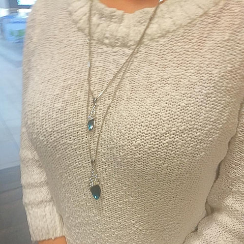 woman wearing blue crystal pendant