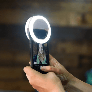 a person holding phone with selfie light