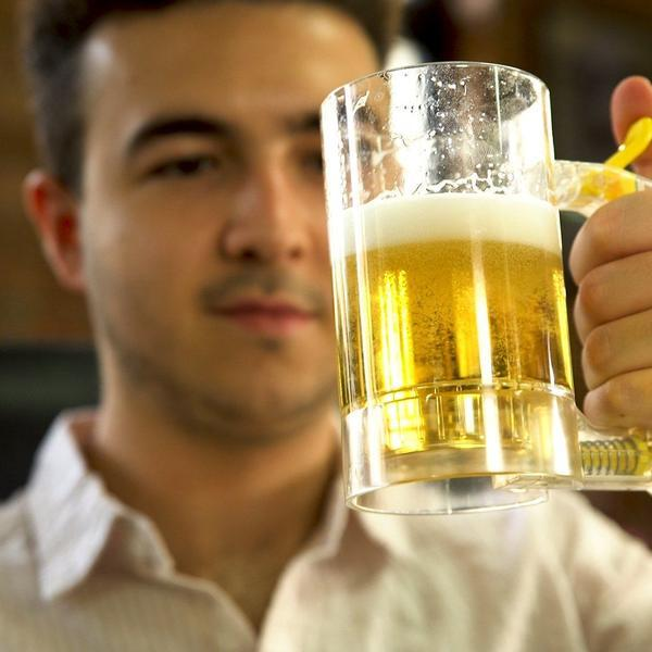 man looking at beer foaming mug in hand
