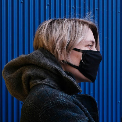 Side view of black cotton face mask on a blonde woman's face