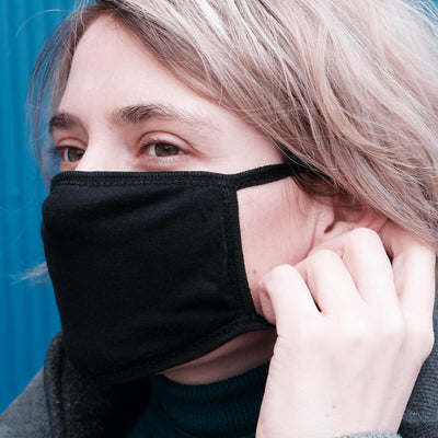 Black cotton face mask on a blonde woman's face