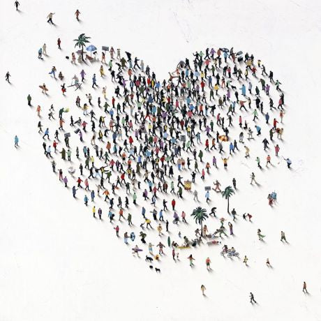 Miniature images of people forming a heart shape, at the beach.