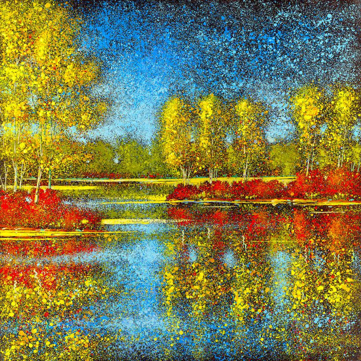 Gold and red trees reflect at the waters edge