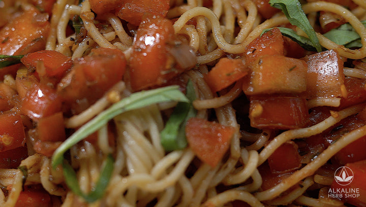 Close up of spaghetti noodles, tomatoes, basil