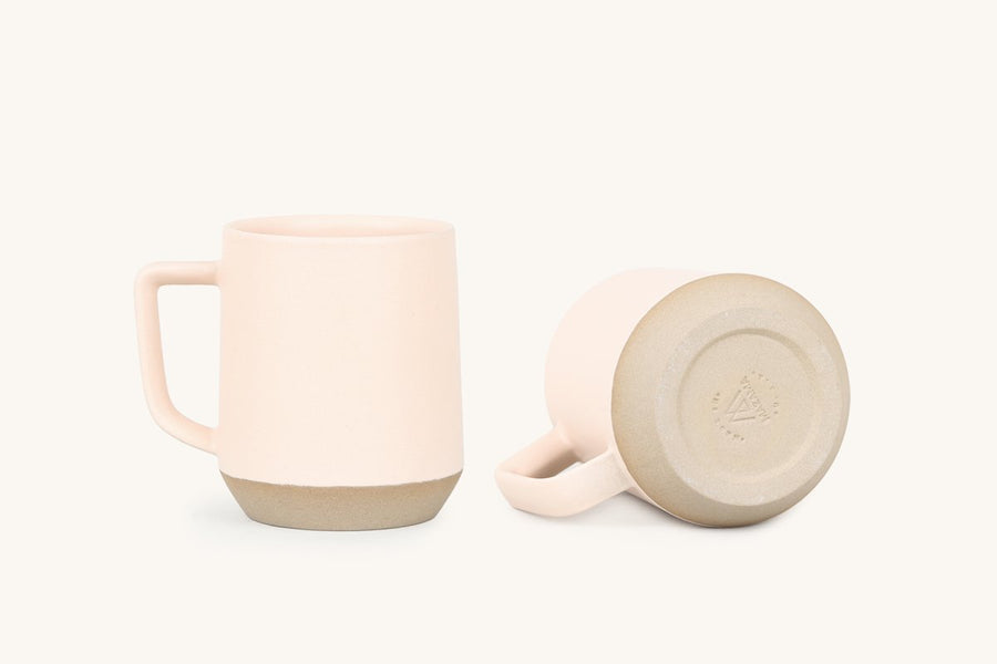 Two peach colored mugs; one upright and one laying down.