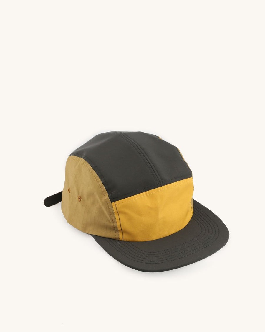 A five panel hat with a black bill and yellow and olive colored panels.