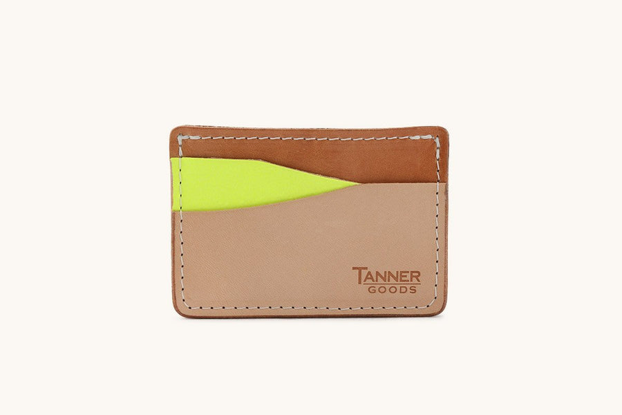 A tri-colored slim leather wallet with a neon yellow card sleeve and Tanner Goods monogram.