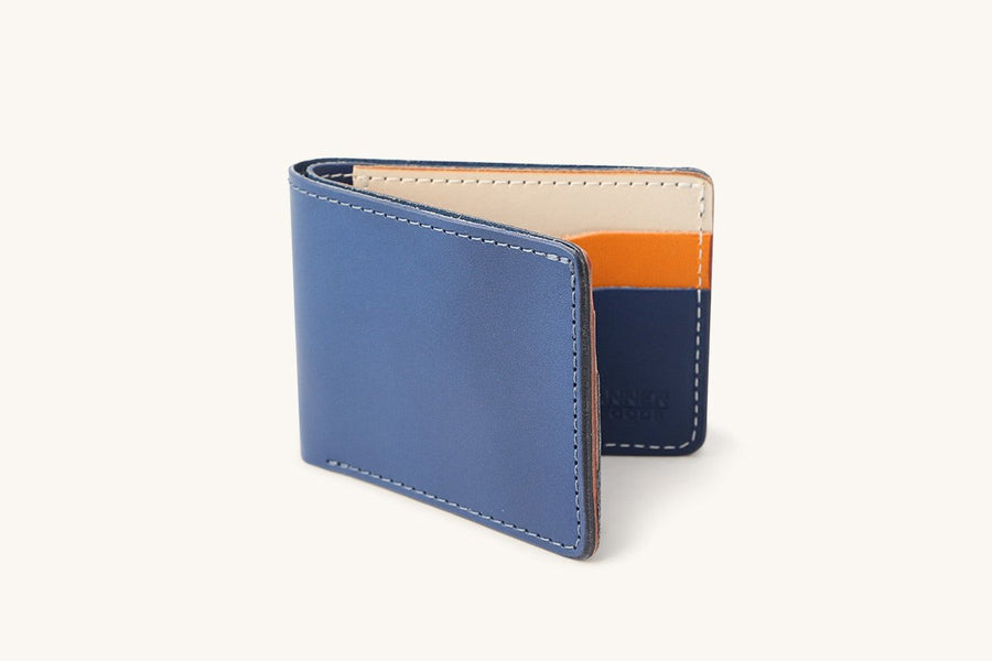 Navy blue colored leather bifold wallet with natural and orange card sleeve slots.
