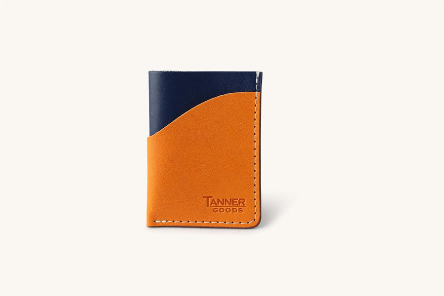 Navy blue minimal card wallet with front leather card sleeve and Tanner Goods monogram.