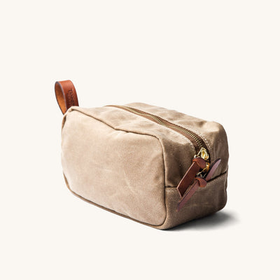 Tan colored dopp kit with leather accents.