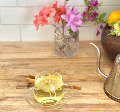 whole flower chrysanthemum tea in a glass tea cup with wooden tongs, a teapot, and flowers.
