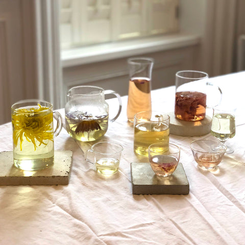 a variety of whole flower teas in a variety of pitchers and glasses