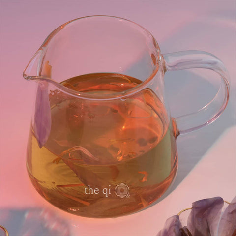 the qi glass tea pitcher or glass server with floral tea and pink background