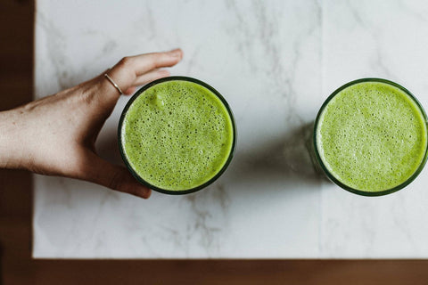 two green juices on the countertop