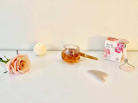 rose with candle, rose tea, gua sha, and rose quartz roller