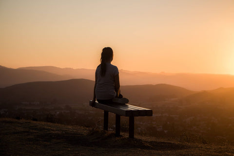 woman sits outside during the sunset to meditate as a wellness ritual