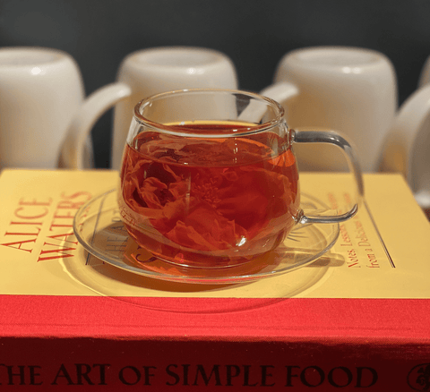 Whole Flower Rose Tea in Glass Teacup On A Stack of Books
