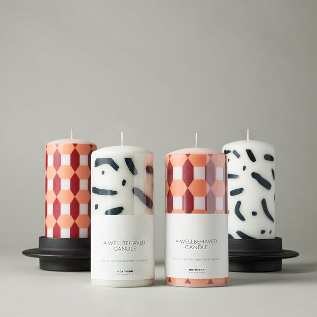 The orange, white and burgundy Salute Milan Block candle as well as the Kampai Osaka Block candle housed in Normann-Copenhagen's Heima Block candleholder