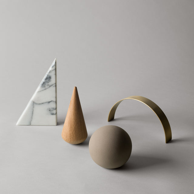 A set of desk sculptures by Kristina Dam Studio that consists of a tigerskin marble bookend, an oak cone, a round terracotta paperweight as well as a brass arc.