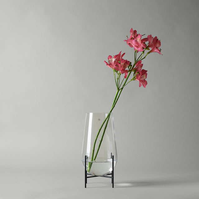 Menu's Echasse vase consists of a clear glass basin elevated by black brass stilts