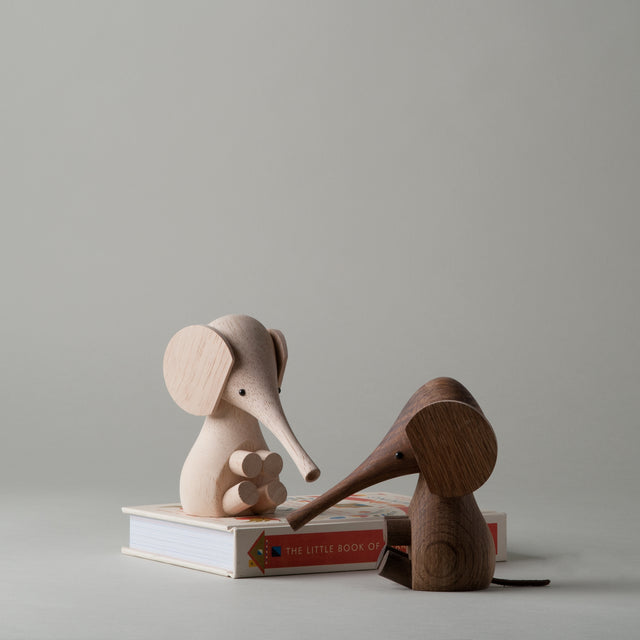 Elephant wooden figures from Lucie Kaas, both have a leather tail and one is crafted with rubber wood while the other is made with smoked oak.