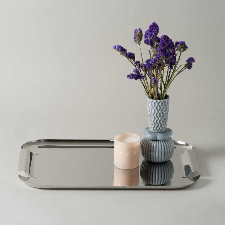 The silver stainless steel Force tray by Normann-Copenhagen, holding a Hygge Skandinavisk candle and a blue Honkabell vase from Finnsdotir.