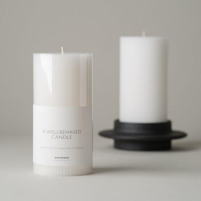 White grooved Block candle from Normann-Copenhagen, housed in the black cast iron Heima Block candleholder.