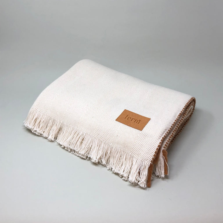 Off-white Herringbone blanket from Ferm Living with a tan brown trim.
