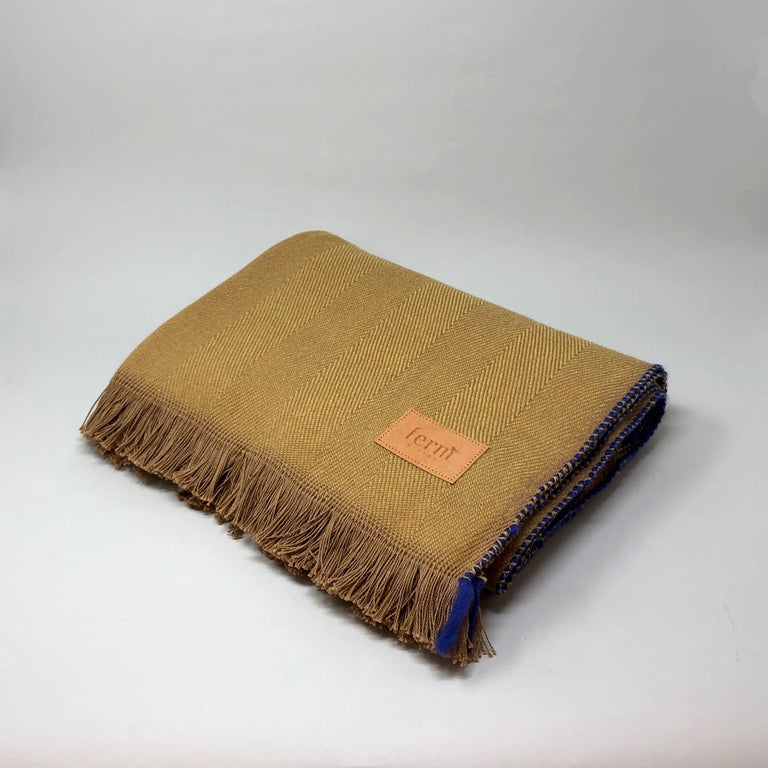 Mustard Herringbone blanket from Ferm Living with a cobalt blue trim.