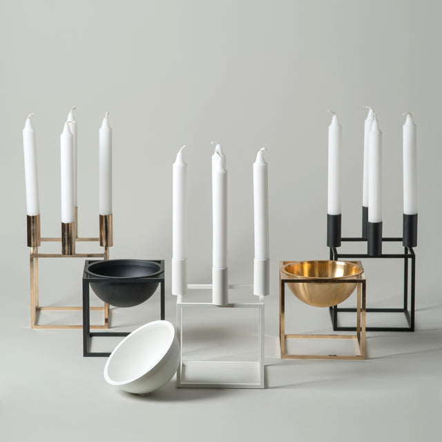 The Kubus collection from By Lassen featuring the Kubus bowl and Kubus candleholder in brass, black and white
