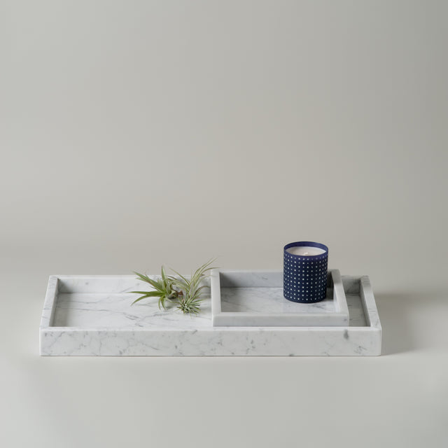 Small and large Hay white Marble trays holding a blue candle from Skandinavisk.