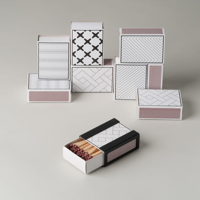 By Lassen black and white matchboxes in exes, grey lines, maze and mesch as well as the black matchbox cover made of steel