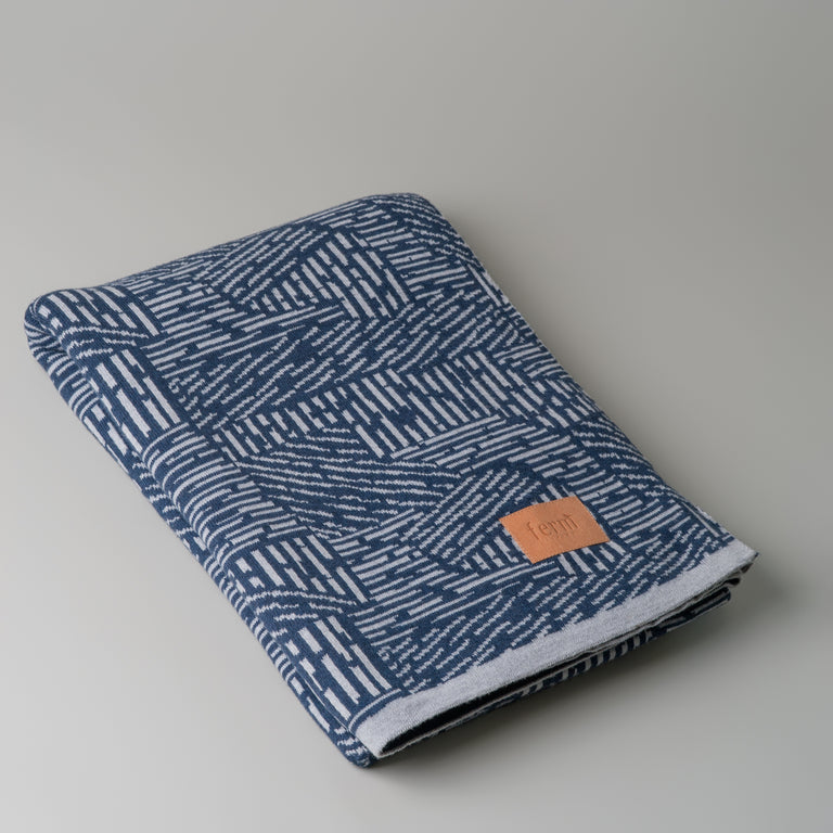 Blue and grey cotton Maze blanket from Ferm Living.