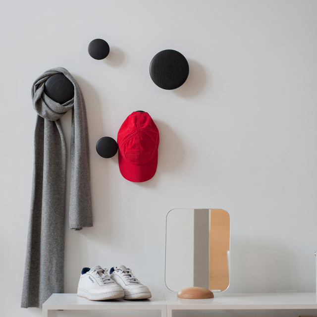 The Dots from Muuto in black, holding a scarf and a hat.