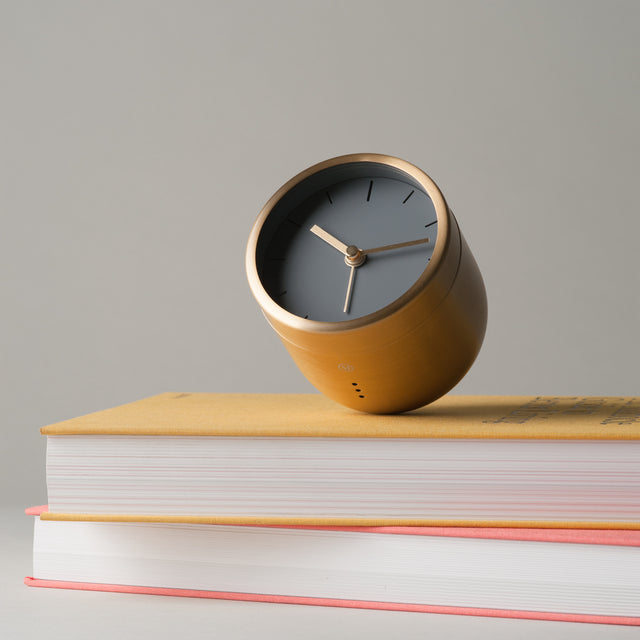 Brass Tumbler alarm clock from Menu sitting on a pile of books.