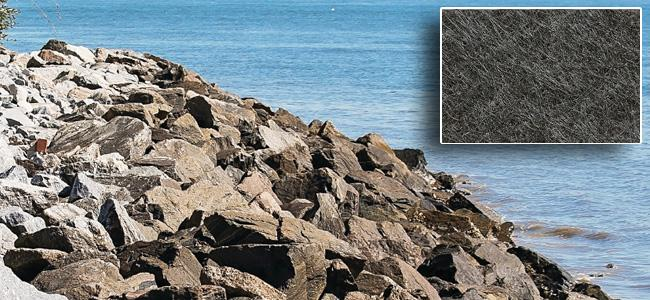 Erosion control fabric on shorline with large breakwater rocks on top