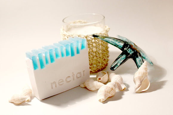 AQUA and white soap with necrar logo with assortment of shells and glass decorations