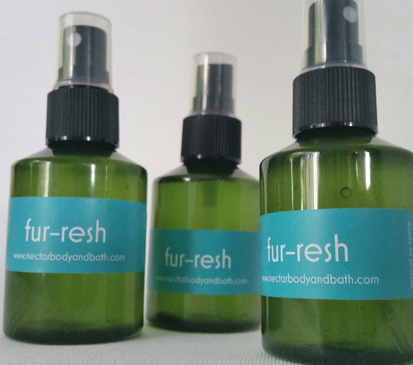 Green spray bottles containing Fur-resh Dog Coat Spray on white background