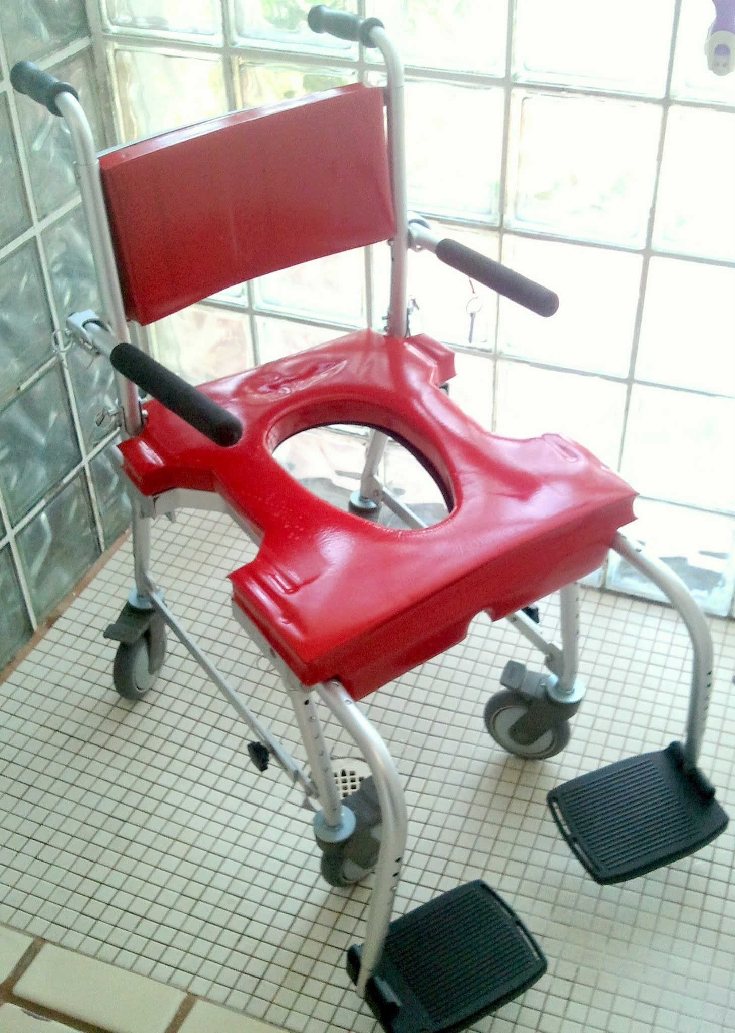 Portable GO-Anywhere Commode 'n Shower Chair (CS) assembled and in roll-in shower – red cushions