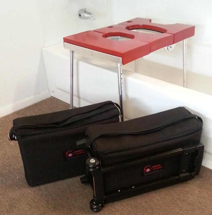 Portable GO-Anywhere Sport Tub Bench (SPT) with Transfer Section assembled and placed over bathtub and travel bags displayed