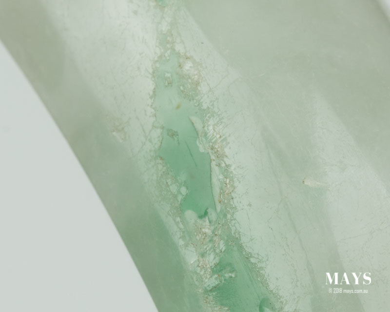 Polymer on the surface of a treated jade bangle has strated to come off