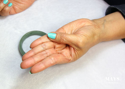 Fold thumb in prepration for fitting jade bangle