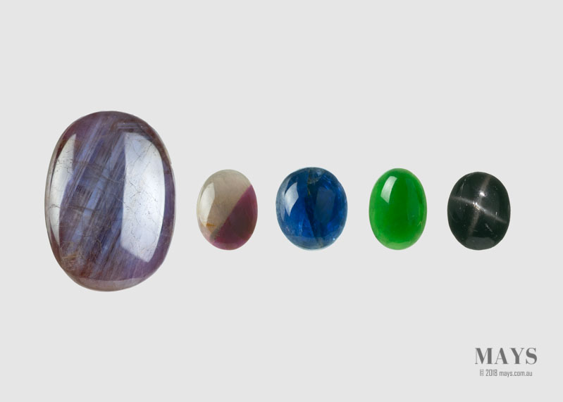 Assorted cabochon gemstones. From the left: Star Sapphire, Parti Sapphire, Blue Sapphire, Jadeite, Star Diopside.