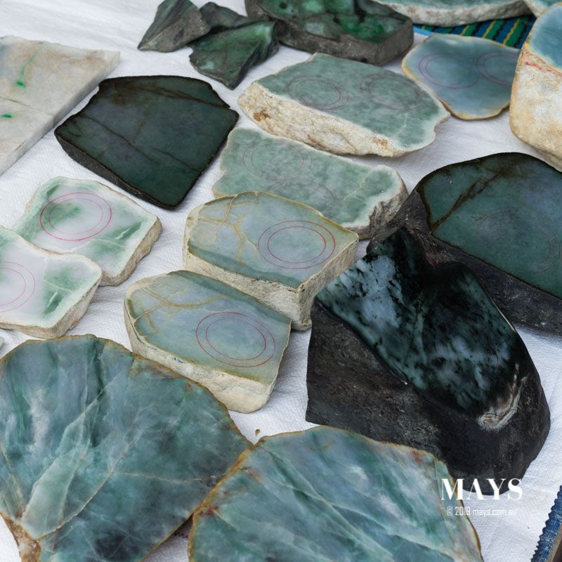 Jadeite slabs and halved boulders for sale by a local vendor at the Jade market in Myanmar.