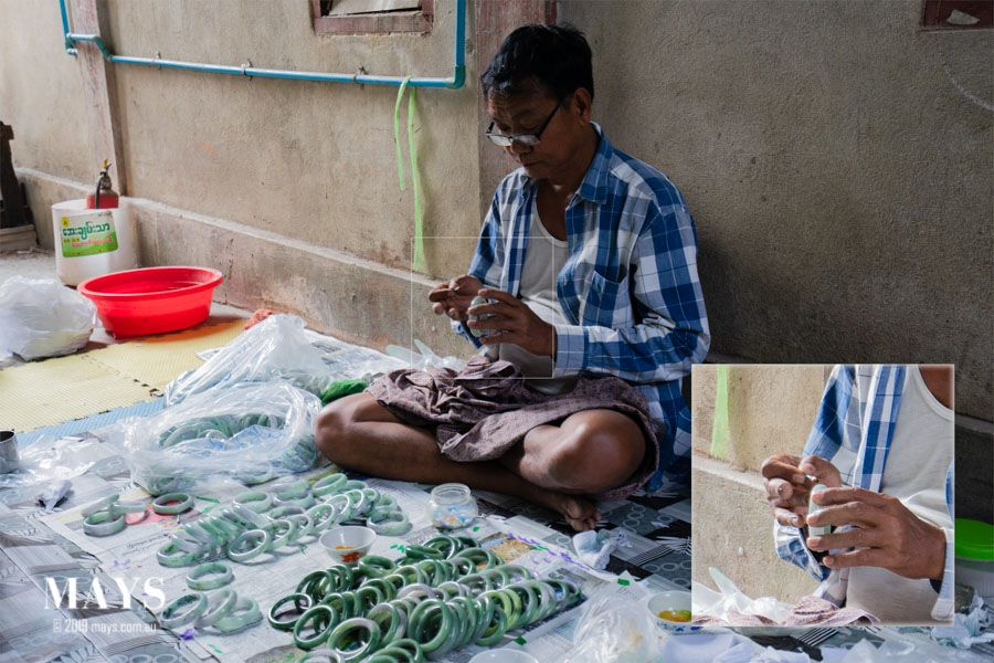 A skilled worker paints dyes on to the jade bangle using a cotton bud. This allows him to precisely create natural looking colour veins and colour patterns.
