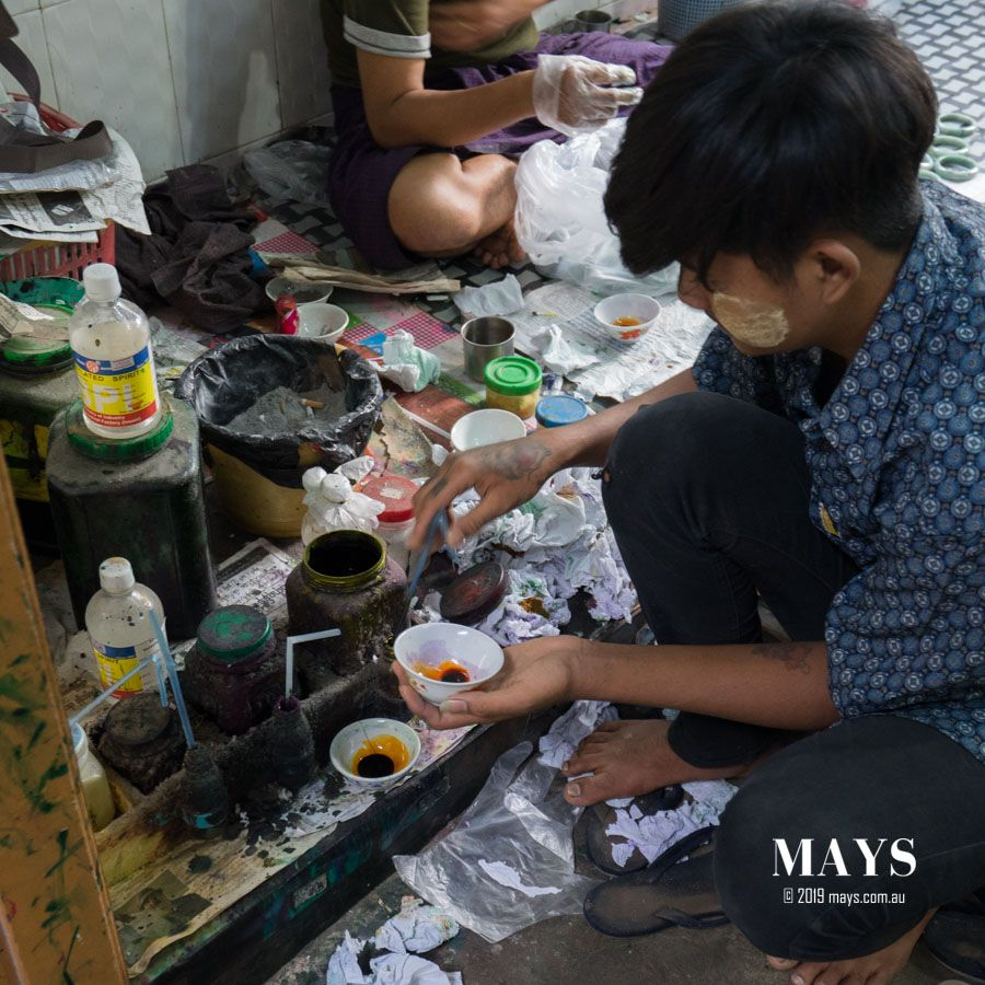 A young man draws out dye concentrates into cups from the mixing station.